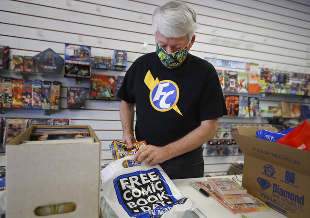 In this photo taken on Wednesday, April 29, 2020, Joe Feld, owner of Flying Color Comics, loads comics into plastic bags for curbside delivery outside his shop in Concord, Calif. The biggest day of the year for comics retailers in America is May 2, Free Comic Book Day, which Feld created. There will be no such day this May, and no comics to populate it after the main distributor stopped shipping product. Will the industry that fuels millions of collectors' superhero dreams and provides fodder for Hollywood's biggest blockbusters be dealt a powerful death blow by the effects of the coronavirus? (AP Photo/Ben Margot)