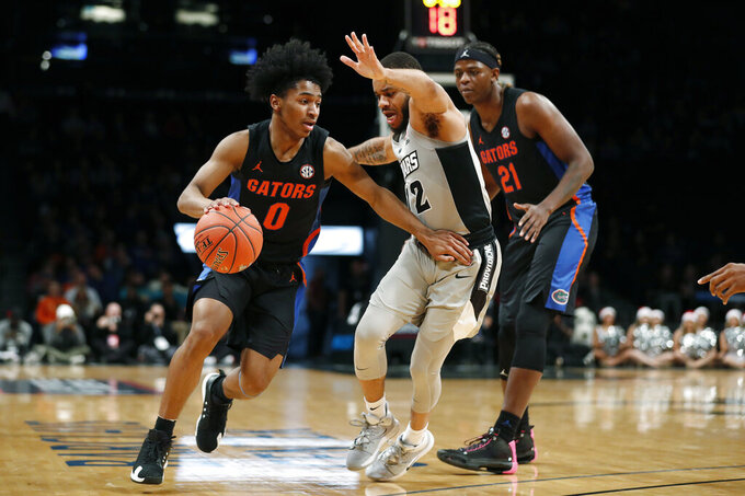 Florida guard Ques Glover (0) drives against Providence guard Luwane Pipkins (12) during the first half of an NCAA college basketball game at Barclays Center, Tuesday, Dec. 17, 2019, in New York. (AP Photo/Michael Owens)