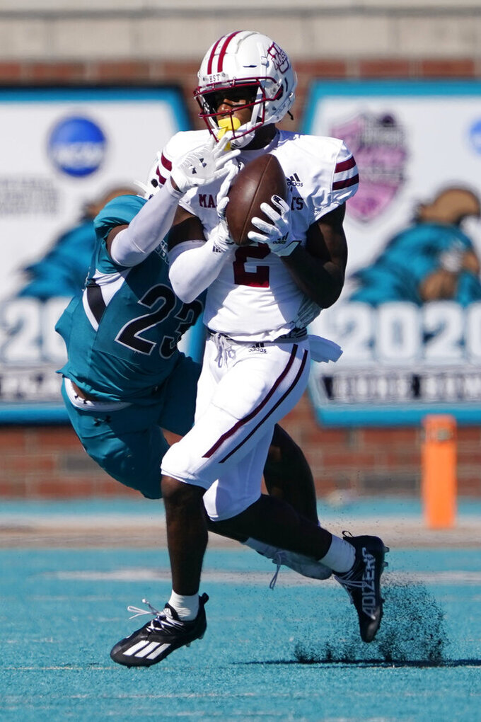 Massachusetts wide receiver Rico Arnold catches a pass in front of Coastal Carolina cornerback Jacob Proche during the second half of an NCAA college football game on Saturday, Sept. 25, 2021, in Conway, S.C. (AP Photo/Chris Carlson)