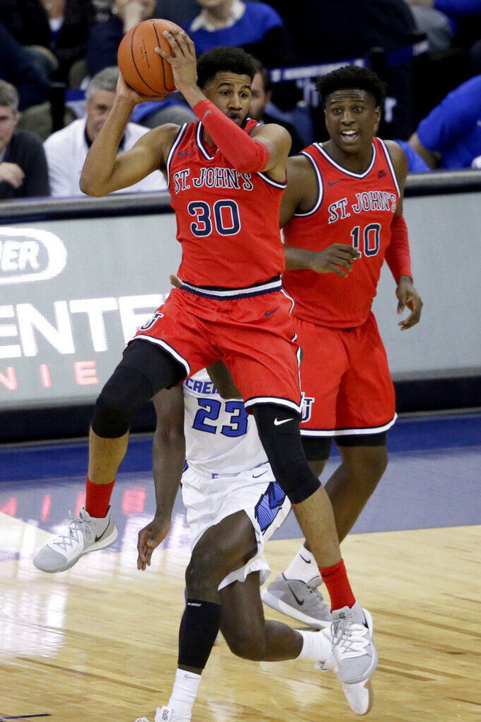 St. John's LJ Figueroa (30) passes the ball in front of Creighton's Damien Jefferson (23) and St. John's Marcellus Earlington (10) during the first half of an NCAA college basketball game in Omaha, Neb., Saturday, Feb. 8, 2020. (AP Photo/Nati Harnik)
