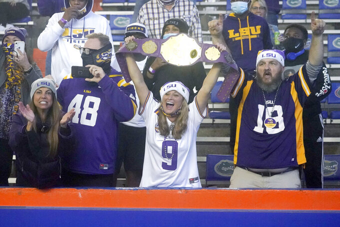LSU fans celebrate after the team's win over Florida in an NCAA college football game Saturday, Dec. 12, 2020, in Gainesville, Fla. (AP Photo/John Raoux)