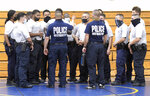 Baltimore city police instructors speak to police trainees during defense tactic training, Wednesday, Aug. 4, 2021, in Baltimore. Baltimore's police force is struggling to meet staffing targets to fully comply with a reform intervention and get out from under federal oversight. The agency has some 400 vacancies among its sworn staff and its recruitment efforts just can't keep pace with those leaving their jobs. (AP Photo/Steve Ruark)