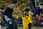 Michigan forward Isaiah Livers (2) drives on Michigan State forward Xavier Tillman (23) in the second half of an NCAA college basketball game in Ann Arbor, Mich., Saturday, Feb. 8, 2020. (AP Photo/Paul Sancya)