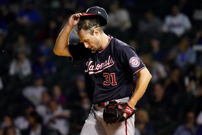 Washington Nationals starting pitcher Max Scherzer adjusts his hat during the fifth inning of a baseball game against the Chicago Cubs in Chicago, Wednesday, May 19, 2021. (AP Photo/Nam Y. Huh)
