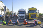 Protesters from Insulate Britain block the A20 which provides access to the Port of Dover, in Kent, England, Friday, Sept. 24, 2021. The environmental activists have moved location after been banned from campaigning on the M25 motorway in London. (Gareth Fuller/PA via AP)