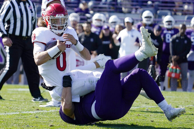 Northwestern defensive tackle Trevor Kent, bottom, tackles Rutgers quarterback Noah Vedral during the second half of an NCAA college football game in Evanston, Ill., Saturday, Oct. 16, 2021. Northwestern won 21-7. (AP Photo/Nam Y. Huh)