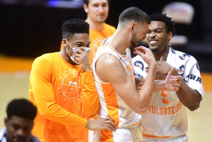 Tennessee forward E.J. Anosike, forward Uros Plavsic and guard Josiah-Jordan James, from left, celebrate after Tennessee defeated Kansas in an NCAA college basketball game in Knoxville, Tenn., Saturday, Jan. 30, 2021. (Caitie McMekin/Knoxville News Sentinel via AP, Pool)