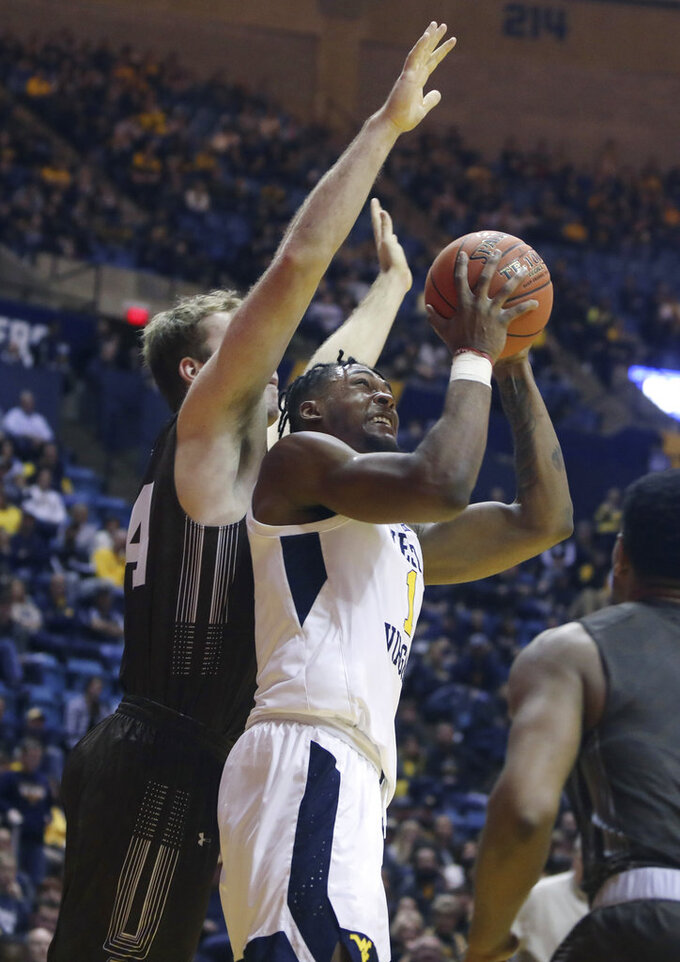 West Virginia forward Derek Culver (1) shoots while defended by Lehigh center James Karnik (13) during the second half of an NCAA college basketball game Sunday, Dec. 30, 2018, in Morgantown, W.Va. (AP Photo/Raymond Thompson)