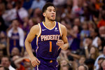 Phoenix Suns guard Devin Booker (1) smiles after making a 3-pointer against the Brooklyn Nets during the second half of an NBA basketball game Sunday, Nov. 10, 2019, in Phoenix. (AP Photo/Matt York)