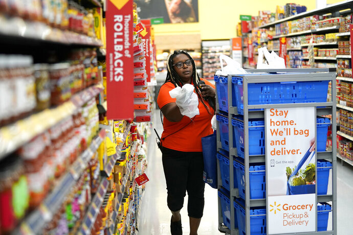FILE - In this Nov. 9, 2018, file photo, Walmart associate Alicia Carter fulfills online grocery orders at a Walmart Supercenter in Houston. Amazon and Walmart on Thursday, April 18, 2019, are kicking off a two-year pilot established by the government to allow low-income shoppers on government food assistance in New York to shop and pay for their groceries online. (AP Photo/David J. Phillip, File)