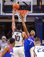 DePaul forward Romeo Weems (1) tries to block the shot of Butler forward Bryce Nze (10) during the second half of an NCAA college basketball game, Saturday, Feb. 29, 2020, in Indianapolis. (AP Photo/Doug McSchooler)