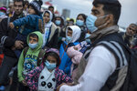 Refugees and migrants wearing masks to prevent the spread off the coronavirus, wait to get on a bus after their arrival at the port of Piraeus , near Athens, on Monday, May 4, 2020. Greek authorities are moving 400 migrants, mostly families, to the mainland to help ease overcrowded conditions at the camp Moria in Lesbos island. (AP Photo/Petros Giannakouris)