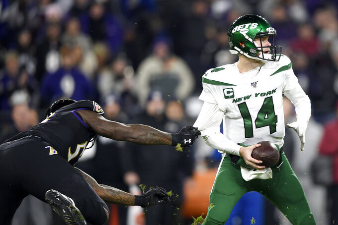 Baltimore Ravens defensive end Jihad Ward, left, grabs at the jersey of New York Jets quarterback Sam Darnold (14) during the first half of an NFL football game, Thursday, Dec. 12, 2019, in Baltimore. (AP Photo/Gail Burton)