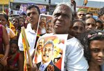 In this Aug 16, 2019, photo, supporters of former Sri Lankan Defense Secretary and opposition's presidential candidate Nandasena Gotabaya Rajapaksa, carry his portrait, and await his arrival in Ambalanthota, Sri Lanka. Gotabaya is a feared former defense official accused of human rights abuses and crushing critics, but to many Sri Lankans, he is the leader most needed after last April's Easter bomb attacks that killed more than 250 people. (AP Photo/Sajeewa Chinthaka)