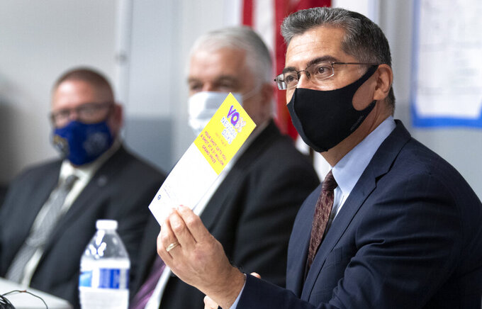 FILE - In this July 22, 2021 file photo, U.S. Department of Health and Human Services (HHS) Secretary Xavier Becerra holds up a flier promoting the Vax Nevada Days lottery after briefing from officials at the Clark County Fire Department Training Facility in Las Vegas.  Most Americans who haven't been vaccinated against COVID-19 say they are unlikely to get the shots and doubt they would work against the aggressive delta variant despite evidence they do, according to a new poll that underscores the challenges facing public health officials amid soaring infections in some states. (Steve Marcus /Las Vegas Sun via AP)