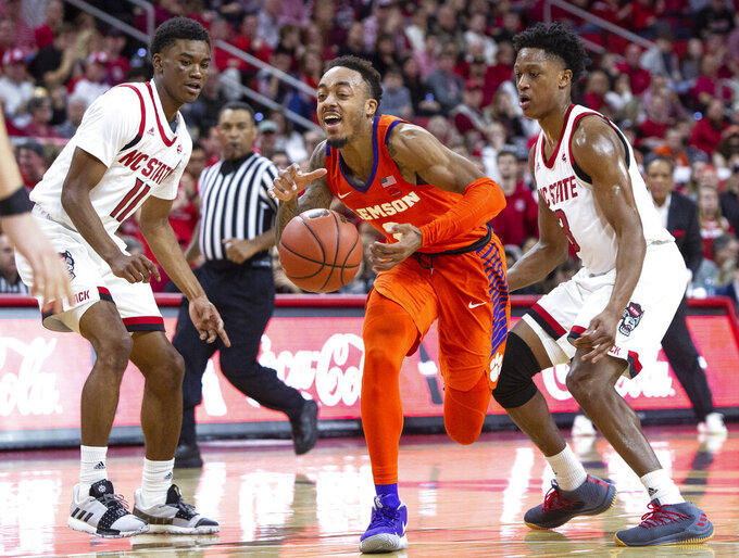 Clemson's Marcquise Reed, middle, loses the ball while driving between North Carolina State's Markell Johnson (11) and C.J. Bryce, right, during the second half of an NCAA college basketball game in Raleigh, N.C., (AP Photo/Ben McKeown)