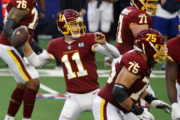 Washington Football Team quarterback Alex Smith (11) throws a pass from the pocket as Brandon Scherff (75) and Wes Schweitzer (71) defend against pressure in the first half of an NFL football game against the Dallas Cowboys in Arlington, Texas, Thursday, Nov. 26, 2020. (AP Photo/Ron Jenkins)