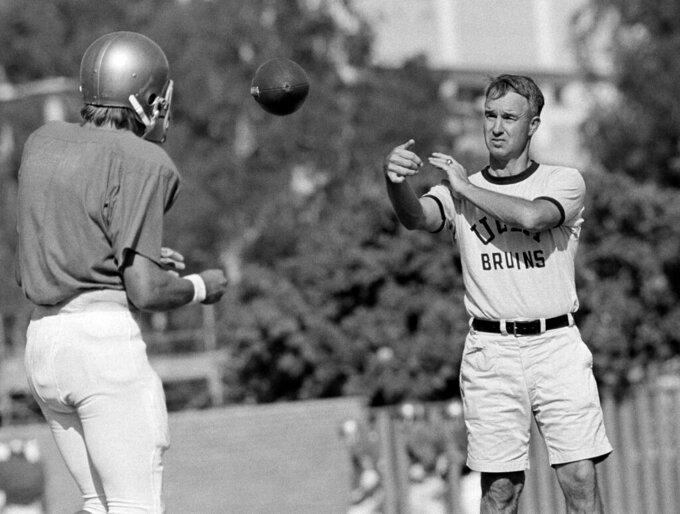 FILE - In this Sept. 13, 1972, file photo, UCLA quarterback Mark Harmon, left, son of former Michigan Heisman Trophy winner Tom Harmon, works out with coach Pepper Rodgers, right, in Los Angeles. Rodgers, a colorful personality who helped Georgia Tech to an unbeaten season as a player in 1952 and went on to coach the Yellow Jackets as well as Kansas, UCLA and in the United States Football League, died Thursday, May 14, 2020, at the age of 88. His alma mater announced his death. A statement from Georgia Tech said Rodgers died in Reston, Va. No cause was given.  (AP Photo/GB, File)