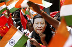 FILE- In this Oct. 10, 2019 file photo, an Indian schoolgirl wears a face mask of Chinese President Xi Jinping to welcome him on the eve of his visit in Chennai, India. Tensions along the China-India border high in the Himalayas have flared again in recent weeks.  Indian officials say the latest row began in early May when Chinese soldiers entered the Indian-controlled territory of Ladakh at three different points, erecting tents and guard posts. (AP Photo/R. Parthibhan, File)