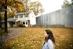 In this Tuesday, Oct. 22, 2019 photo, Carrie Gross walks past a construction barrier shielding the Mariner East pipeline near a home during an interview with The Associated Press in Exton, Pa. The pipeline route traverses those suburbs, close to schools, ballfields and senior care facilities.