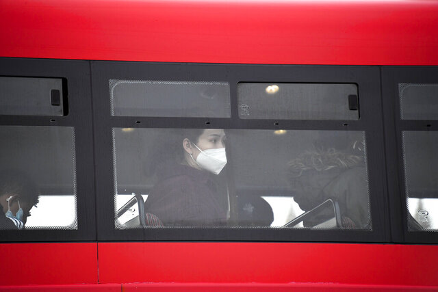 A woman wears a face mask as she sits on a bus, in London, Wednesday, Oct. 7, 2020. Like other countries in Europe, the U.K. has seen rising coronavirus infections over the past few weeks, which has prompted the government to announce a series of restrictions, both nationally and locally, to keep a lid on infections. (AP Photo/Alberto Pezzali)