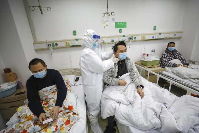 A doctor checks the conditions of a patient in Jinyintan Hospital, designated for critical COVID-19 patients, in Wuhan in central China's Hubei province Thursday, Feb. 13, 2020. China on Thursday reported 254 new deaths and a spike in virus cases of 15,152, after the hardest-hit province of Hubei applied a new classification system that broadens the scope of diagnoses for the outbreak, which has spread to more than 20 countries. (Chinatopix Via AP)