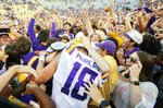 LSU's Foster Moreau (18) is surrounded as fans rush the field after the Tigers 36-16 win over Georgia in an NCAA college football in Baton Rouge, La., Saturday, Oct. 13, 2018. (AP Photo/Matthew Hinton)