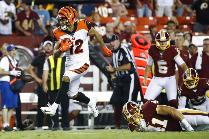 Cincinnati Bengals' Alex Erickson (12) gets away from Washington Redskins' Matt Flanagan (41) as he returns a punt for a touchdown during the second half of an NFL preseason football game Thursday, Aug. 15, 2019, in Landover, Md. The Bengals won 23-13. (AP Photo/Alex Brandon)