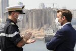 Arnaud Tranchant, left, chief Navy officer for the French helicopter carrier Tonnerre, talks to French President Emmanuel Macron off the port of Beirut, Tuesday, Sept.1, 2020. The visit was Emmanuel Macron's second since the devastating Aug. 4 explosion — the most destructive single incident in Lebanon's history — that killed at least 190 people . (Stephane Lemouton, Pool via AP)