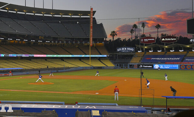 The Los Angeles Dodgers play the Los Angeles Angels at sunset during the fifth inning of a preseason baseball game, Tuesday, July 21, 2020, in Los Angeles. (AP Photo/Mark J. Terrill)