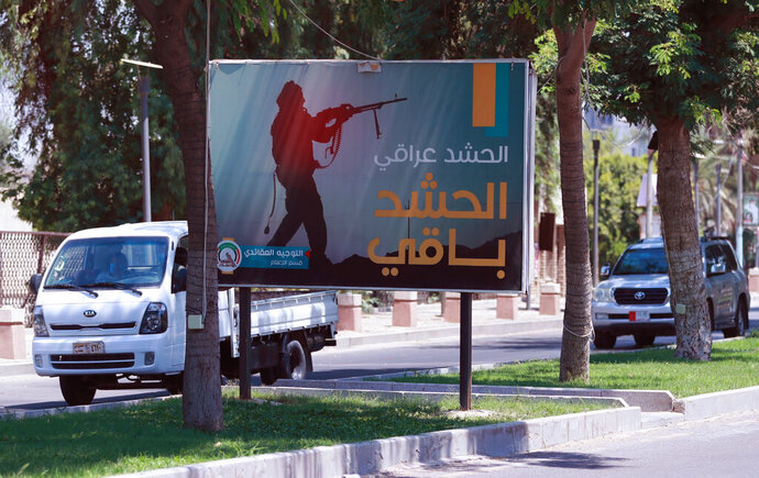 Motorists pass by a Popular Mobilization poster in Baghdad, Iraq, Friday, June 26, 2020. Iraqi security forces arrested over a dozen men suspected of a spate of rocket attacks against the U.S. (AP Photo/Hadi Mizban)