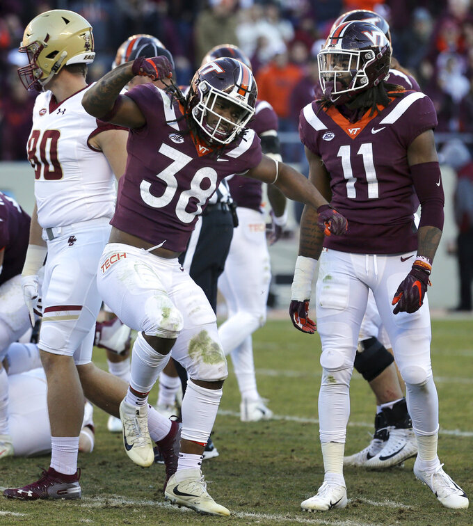 Virginia Tech linebacker Rico Kearney (38) and Houshun Gaines (11) celebrate a Virginia Tech defensive stop in the first half of an NCAA college football game in Blacksburg Va., Saturday, Nov. 3, 2018. (Matt Gentry/The Roanoke Times via AP)