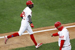 Philadelphia Phillies' Roman Quinn, left, celebrates with thirdbase coach Dusty Wathan after hitting a home run off Atlanta Braves pitcher Sean Newcomb during the second inning of a baseball game, Monday, Aug. 10, 2020, in Philadelphia. (AP Photo/Matt Slocum)