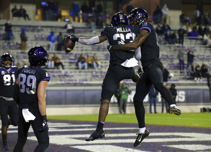 TCU running back Kendre Miller (33) celebrates with wide receiver Savion Williams (18) after a third quarter touchdown against Louisiana Tech during an NCAA college football game, Saturday, Dec. 12, 2020. (AP Photo/ Richard W. Rodriguez)