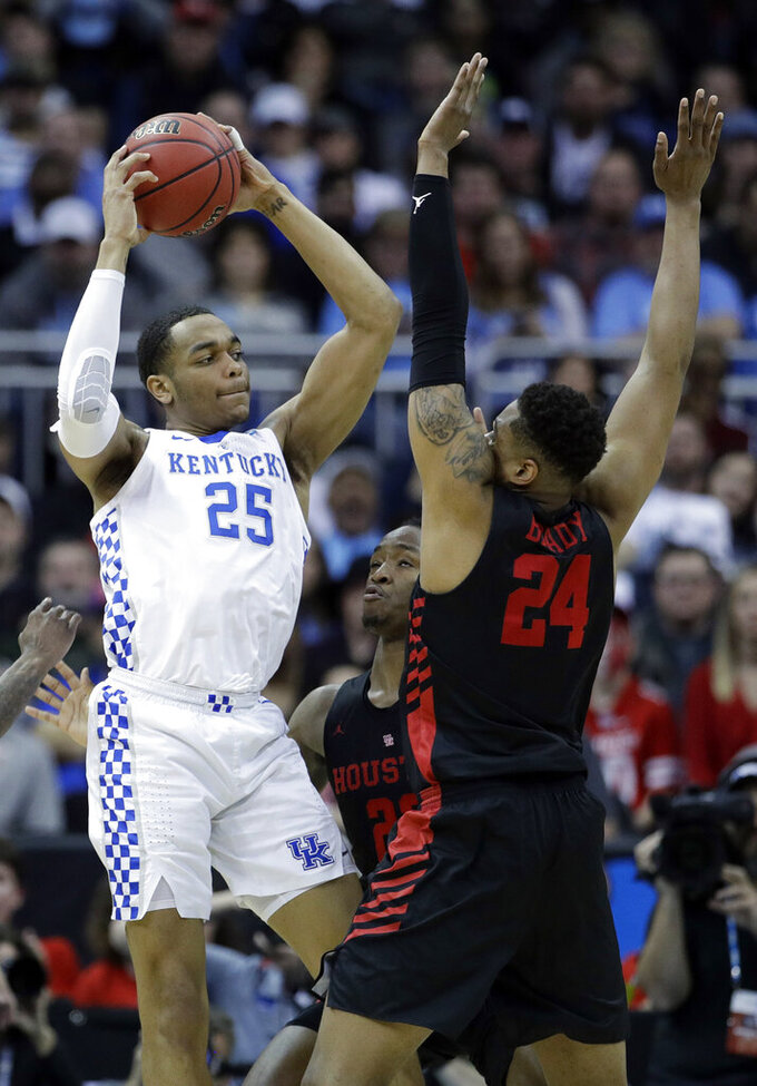 Kentucky's PJ Washington (25) passes over Houston's Cedrick Alley Jr. and Houston's Breaon Brady (24) during the first half of a men's NCAA tournament college basketball Midwest Regional semifinal game Friday, March 29, 2019, in Kansas City, Mo. (AP Photo/Charlie Riedel)
