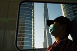 FILE - In this April 26, 2020 file photo, a commuter wearing a face mask to help curb the spread of the coronavirus, sleeps aboard the driverless Metro as it passes the Burj Khalifa, the world's tallest building, in Dubai, United Arab Emirates. The confirmed death toll from the coronavirus has gone over 50,000 in the Middle East as the pandemic continues. That's according to a count Thursday, Sept. 3, 2020, from The Associated Press, based on official numbers offered by health authorities across the region. (AP Photo/Jon Gambrell, File)