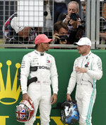 Mercedes driver Valtteri Bottas of Finland, right, speaks with second placed Mercedes driver Lewis Hamilton of Britain after he clocked the fastest time during the qualifying session at the Silverstone racetrack, in Silverstone, England, Saturday, July 13, 2019. The British Formula One Grand Prix will be held on Sunday. (AP Photo/Luca Bruno)
