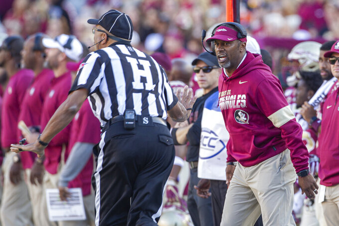 Florida State head coach Willie Taggart, right, disagrees with the referee in the first half of an NCAA college football game against Miami in Tallahassee, Fla., Saturday, Nov. 2, 2019. (AP Photo/Mark Wallheiser)