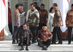 Newly appointed Defense Minister Prabowo Subianto, center, walks past Indonesian President Joko Widodo, seated left, his former rival in last April's election and Vice President Ma'ruf Amin, seated right, during the announcement of the new cabinet ministers at Merdeka Palace in Jakarta, Indonesia, Wednesday, Oct. 23, 2019. (AP Photo/Dita Alangkara)