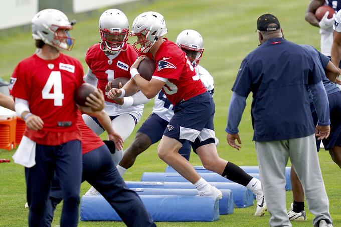 New England Patriots quarterbacks Jarrett Stidham (4), Mac Jones (50) and Cam Newton (1) run drills during NFL football practice in Foxborough, Mass., Friday, June 4, 2021. (AP Photo/Mary Schwalm)