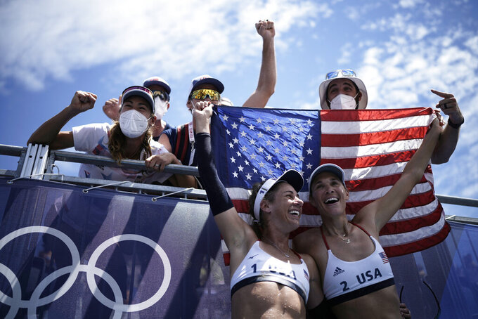 April Ross, left, of the United States, and teammate Alix Klineman celebrate winning a women's beach volleyball gold medal match against Australia at the 2020 Summer Olympics, Friday, Aug. 6, 2021, in Tokyo, Japan. (AP Photo/Felipe Dana)