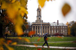 """FILE - In this Oct. 28, 2015 file photo, a Penn State student walks in the rain past Old Main on the Penn State main campus in State College, Pa.  Lawmakers are trying to stop 144 cities across the U.S. from losing their designations as """"metropolitan areas"""" because the federal government is upgrading the standard from a minimum of 50,000 residents in its core to a minimum of 100,000 people. State College is among the cities at risk of losing the designation.   (AP Photo/Gene J. Puskar, File)"""