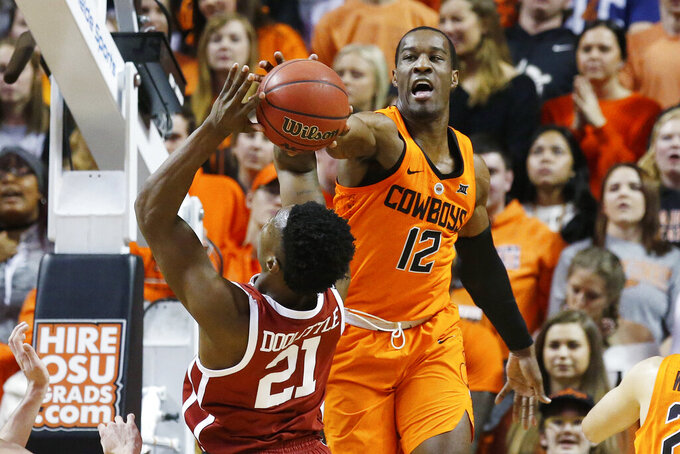 FILE - In this Jan. 23, 2019, file photo, Oklahoma State forward Cameron McGriff (12) blocks a shot by Oklahoma forward Kristian Doolittle (21) during the first half of an NCAA college basketball game in Stillwater, Okla. The Cowboys have a trio of senior captains who are primed to lead the Cowboys back to prominence - Lindy Waters III, Cameron McGriff and Thomas Dziagwa (AP Photo/Sue Ogrocki, File)