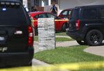 A crime scene photographer takes a photo of a vehicle in the driveway of a home where multiple people were killed and one was hospitalized after a shooting at a home in the Remington Park neighborhood of Ponder, Texas on Wednesday, May 16, 2018. (Rose Baca/The Dallas Morning News via AP)