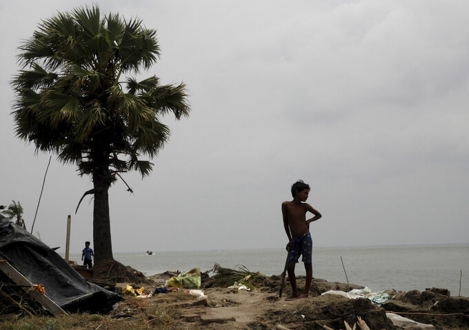 This May 22, 2020 photo shows a boy looking at the damage caused by Cyclone Amphan in Deulbari village, in South 24 Parganas district in the Sundarbans, West Bengal state, India. The cyclone that struck India and Bangladesh last month passed through the Sundarbans, devastating the islands that are home to one of the world's largest mangrove forests and is a UNESCO world heritage site. (Samrat Paul via AP)