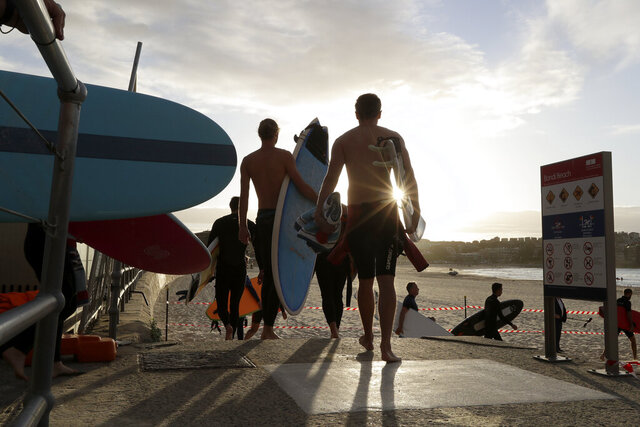 Surfers walk onto the sand to prepare to enter the water at Bondi Beach in Sydney, Tuesday, April 28, 2020, as coranavirus pandemic restrictions are eased. The beach is open to swimmers and surfers to exercise only. (AP Photo/Rick Rycroft)