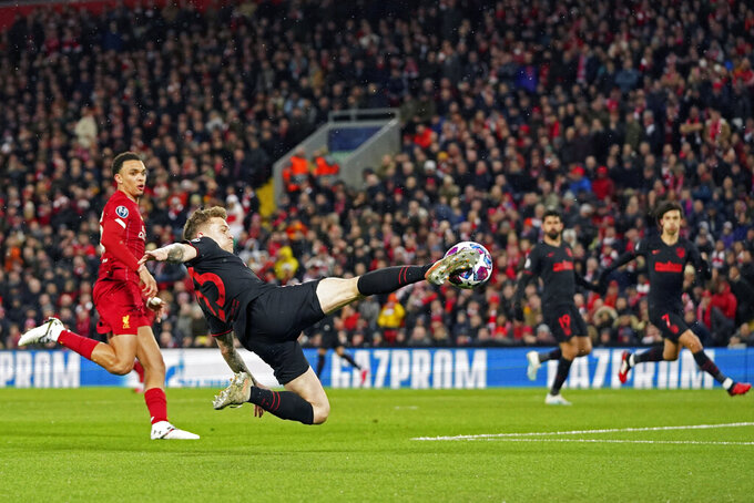 Atletico Madrid's Kieran Trippier attempts a shot at goal in front of Liverpool's Trent Alexander-Arnold during a second leg, round of 16, Champions League soccer match between Liverpool and Atletico Madrid at a packed Anfield stadium in Liverpool, England, Wednesday, March 11, 2020. (AP Photo/Jon Super)
