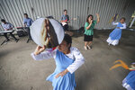 People sing and dance during a religious service at the Oasis of Peace evangelical church in Managua, Nicaragua, Sunday, Aug. 16, 2020. Evangelical churches have kept spreading the Gospel despite government measures meant to slow the spread of the novel coronavirus. (AP Photo/Alfredo Zuniga)