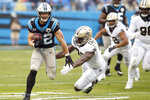 Carolina Panthers running back Christian McCaffrey (22) runs as Carl Granderson (96) reaches for the tackle during the second half of an NFL football game in Charlotte, N.C., Sunday, Dec. 29, 2019. McCaffrey broke a record on the play to become the third player in NFL history to tally 1000 rushing and 1000 receiving yards in the same season. (AP Photo/Brian Blanco)