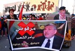 Protesters chant slogans while holding a poster of newly-appointed Prime Minister Mohammed Allawi with Arabic that reads,